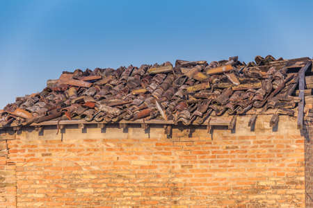 drooping: roof in disrepair with drooping broken tiles of abandoned country house in Italy