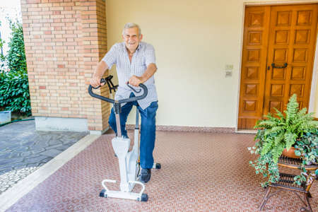 senior adults: elderly octogenarian male keeps fit by doing exercise bike on the patio of the house