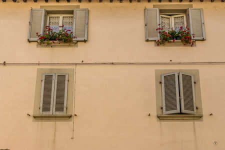 red shutters: vintage square windows with shutters  pots of red hanging geraniums