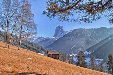 lodge: Mountain lodge on brownish orange grass in valley of pine forests and snow-capped peaks in winter