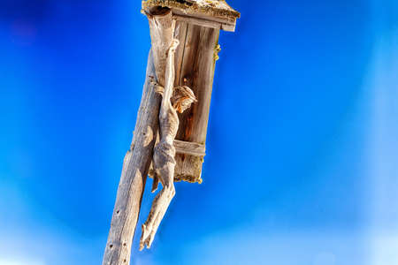 crucify: Wood-carved statue of crucifixion of Jesus Christ. Wood shows signs of weathering