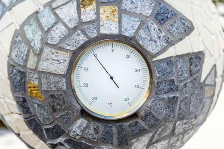 analogue: Temperature just below zero Celsius marked by a analogue environmental  thermometer cemented into a mosaic of stones