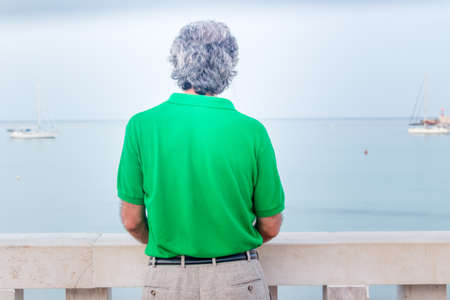 seaside town: back of charming middle-aged man in green polo in a seaside town Stock Photo