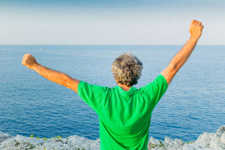 back of a charming middle-aged man in green polo stretching arms in a seaside town Stock Photo