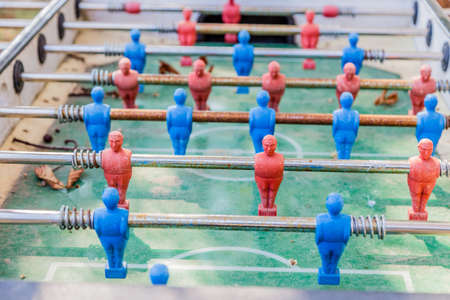 dirty football: details of red and blue table football dummy players, dirty and rusty, covered with leaves and dust