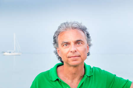 seaside town: charming middle-aged man in green polo in a seaside town Stock Photo