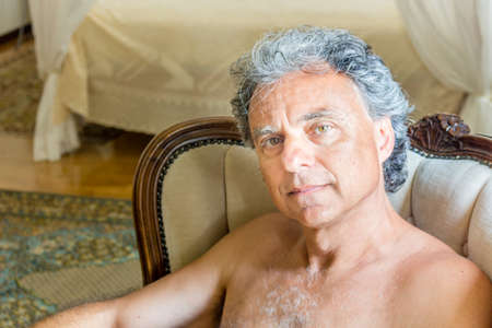 easy chair: Handsome shirtless tanned man sitting on easy chair in the living room Stock Photo