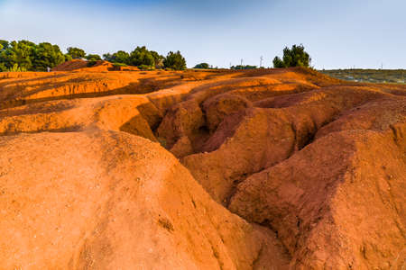 red soils around the freshwater lake formed in a former quarry for the extraction of bauxite in Italy