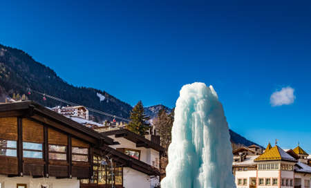 gardena: Frozen ice fountain in snowy alpine village in Italy illuminated by sun with mountains in the background Stock Photo