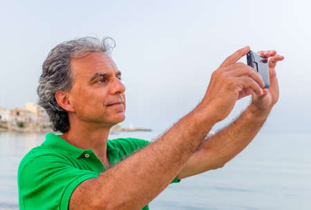 seaside town: Handsome man in green polo takes a selfie in a seaside town