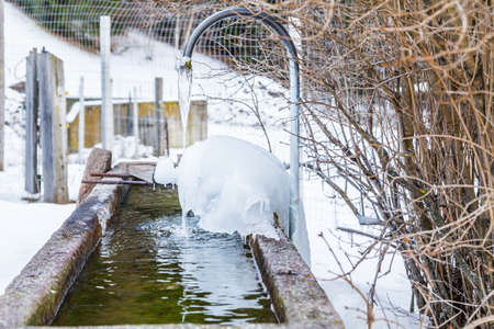 italian fountain: icycles in frozen peeling fountain in the Italian Alps Stock Photo