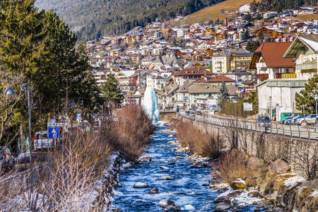 gardena: River passing through snowy alpine village in Italy illuminated by sun with mountains in the background