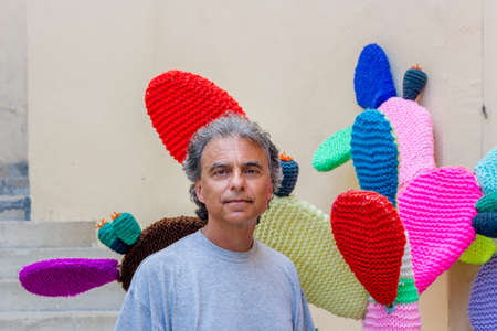 paddles: middle-aged man in gray t-shirt on vacation near a fake cactus Knitted with multicolored paddles