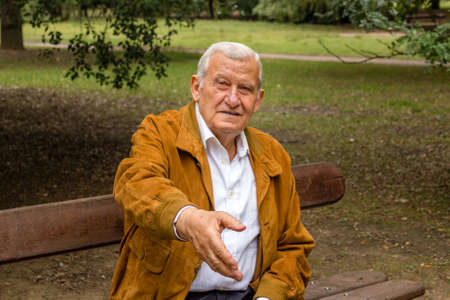 gives: senior with suede jacket and white shirt in a green park gives his hand to shake Stock Photo