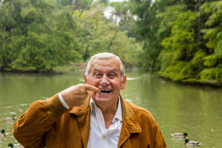 indicates: senior with suede jacket and white shirt in a green park indicates dentures