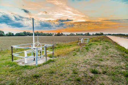 means: Gears and operating means to manage channel to divert river water for irrigation of cultivated fields Stock Photo