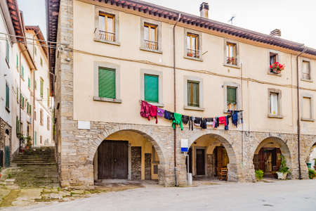 characterized: Alleys in medieval mountain village in Tuscany characterized by houses with walls of stones derived from the Renaissance: typical Italian details as pots of flowers and drying cable with clothes hanging out to dry Stock Photo