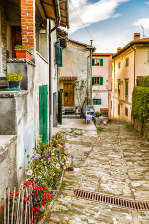 characterized: Alleys in medieval mountain village in Tuscany characterized by houses with walls of stones derived from the Renaissance: typical Italian details as pots of flowers and drying rack with clothes hanging out to dry