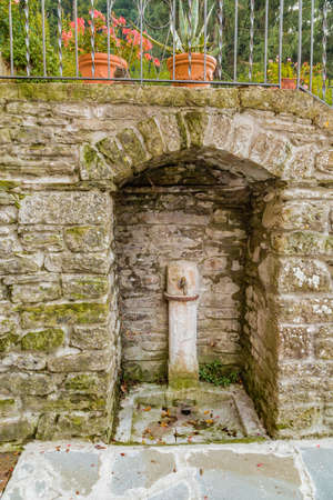 characterized: Fountain in medieval mountain village in Tuscany characterized by houses with walls of stones derived from the Renaissance