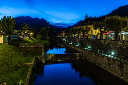 characterized: River runs through medieval mountain village in Tuscany characterized by houses with walls of stones derived from the Renaissance. Night view Stock Photo