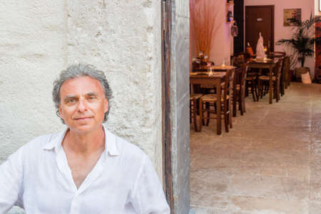 gargano: middle-aged man in white shirt  sitting at the restaurant while visiting the old streets of ancient town, Vieste in Italy, known as the Pearl of Gargano