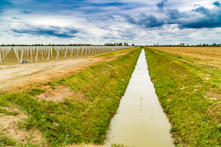 precast: irrigation canal divides harvested land  and plowed land with precast piles