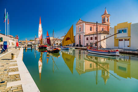 Reflection of church and ancient boats on Canal Port in Cesenatico Stock Photo