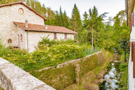 characterized: Small stream runs trhough medieval mountain village in Tuscany characterized by houses with walls of stones derived from the Renaissance Stock Photo