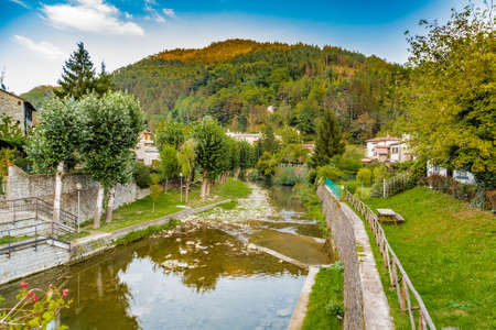characterized: River runs thorugh medieval mountain village in Tuscany characterized by houses with walls of stones derived from the Renaissance