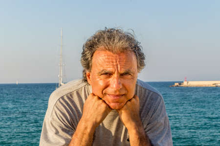 seaside town: Smiling and tanned middle-aged Caucasian man relaxing on vacation, holding his chin in front of the breathtaking panorama of an Italian seaside town