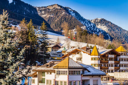valley view: The roofs of a people friendly alpine town in the background of snowy mountains in the Italian Alps