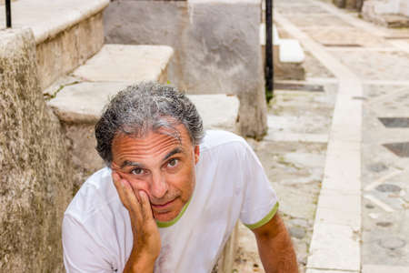 gargano: middle-aged man in sportswear sitting while visiting the ancient alleys of a medieval town suspended in time, Vico del Gargano in Italy, known as the Village of Love Stock Photo