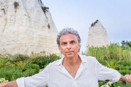 gargano: middle-aged man in white shirt while visiting the cliffs of ancient town, Vieste in Italy, known as the Pearl of Gargano