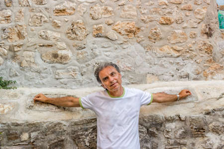 foggia: middle-aged man in sportswear while visiting the ancient alleys of a medieval town suspended in time, Vico del Gargano in Italy, known as the Village of Love