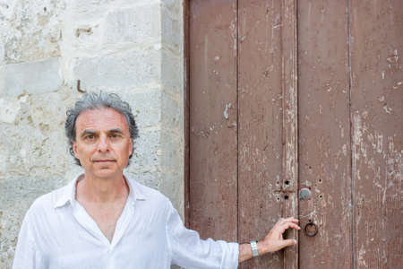 foggia: middle-aged man in white shirt while visiting the old streets of ancient town, Vieste in Italy, known as the Pearl of Gargano