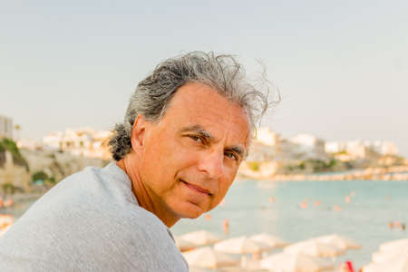 seaside town: Smiling and tanned middle-aged Caucasian man relaxing on vacation,  in front of the breathtaking panorama of an Italian seaside town