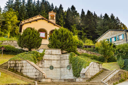 characterized: Church and fountain in medieval mountain village in Tuscany characterized by houses with walls of stones derived from the Renaissance