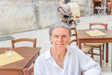 foggia: middle-aged man in white shirt  sitting at the restaurant while visiting the old streets of ancient town, Vieste in Italy, known as the Pearl of Gargano
