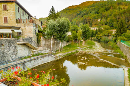 derived: River runs thorugh medieval mountain village in Tuscany characterized by houses with walls of stones derived from the Renaissance