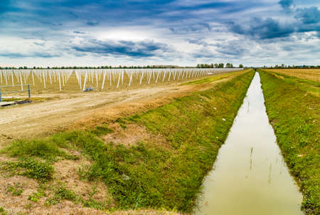 irrigation field: irrigation canal divides harvested land  and plowed land with precast piles