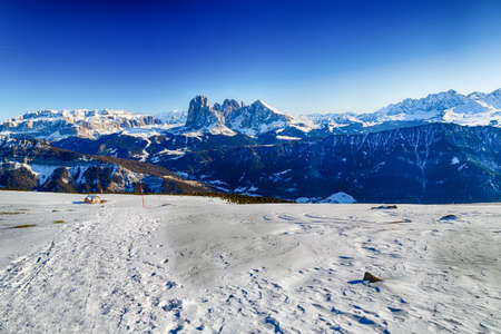 snowcapped: Lonely cottage on a bcakground of White snowy Dolomites mountains with rocks, snow-capped peaks and green conifers in winter