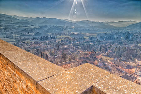 parapet: Parapet on tile roofs of Italian country village in a winter foggy and sunny day