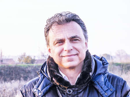 ojos verdes: Elegant middle-aged man with green eyes and  salt pepper hair dressed in dark blue padded jacket is smiling reassuringly in the countryside Foto de archivo