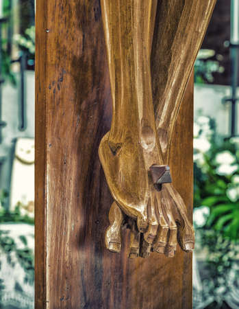crucify: the detail of nailed feetr in a wood carved statue  of the Crucifixion of Jesus Christ
