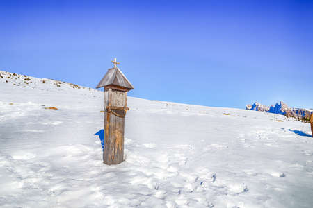 votive: votive shrine in the snow in the high mountains showing the Crucifixion of Jesus Christ Stock Photo