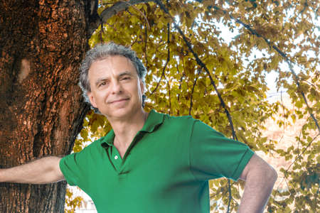 greeen: cute man in greeen polo smilling under the leaves of a green tree Stock Photo