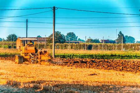 arando: old tractor is plowing a field in Italian countryside