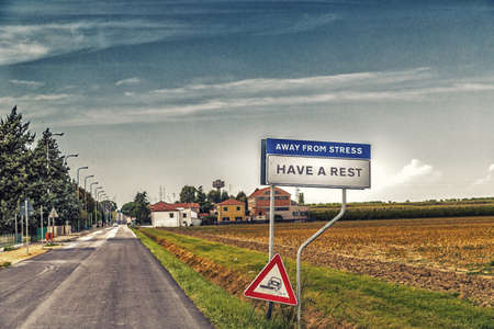 have on: fake road sign of a quiet countryside village inviting to have a rest away from stress Stock Photo