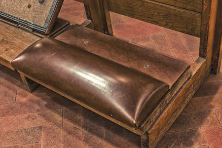repentance: kneeler with leather cushion to support the knees of the faithful who pray in a Catholic Italian church