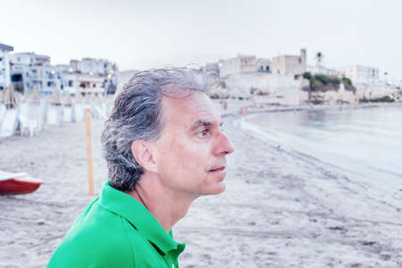 seaside town: side view of charming middle-aged man in green polo in a seaside town